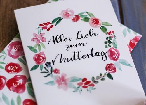 """Weiße Klappkarte mit dem Handlettering Schriftzug """"Alles Liebe zum Muttertag"""" umrankt von einem Blumenkreis aus Aquarell"""