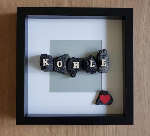 Schwarzer Bilderrahmen mit einer Collage aus Kohle auf der kleine Holzbuchstaben angebracht sind, welche das Wort Kohle buchstabieren
