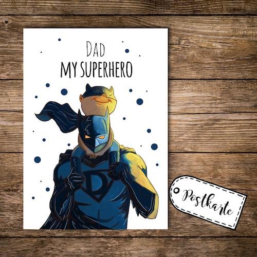 Postkarte mit Superhero Illustration in Blautönen, Superhero mit D-Logo auf der Brust trägt einen kleinen Sidekick auf den Schultern, Aufschrift oberhalb der Illustration: Dad My Superhero