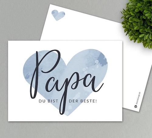 """Hochglanz Postkarte mit blauem Herz im Wasserfarbenlook und einem dem Aufdruck """"Papa du bist der Beste!"""" im Vordergrund"""