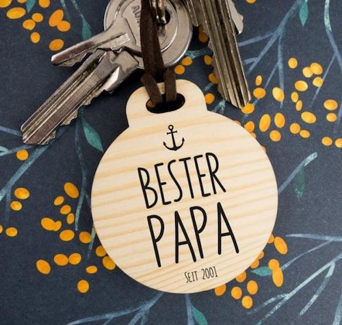 """Runder Schlüsselanhänger aus Holz mit der Gravur eines kleinen Ankers und dem Schriftzug """"Bester Papa seit Datum"""""""