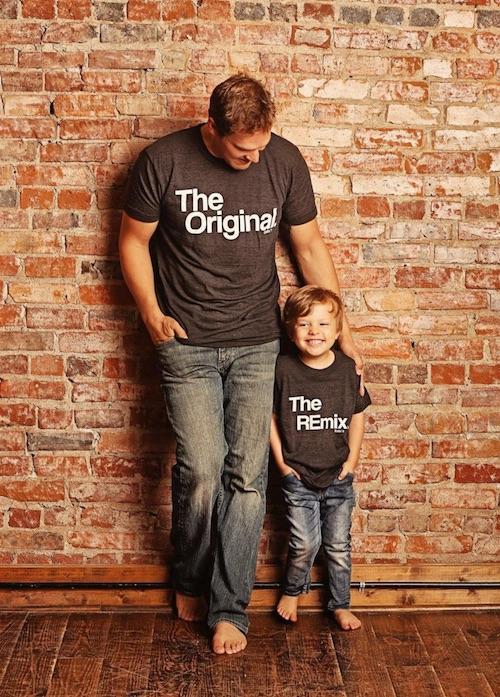Vater und Sohn mit zusammengehörenden T-Shirts vor einer Klinkerwand